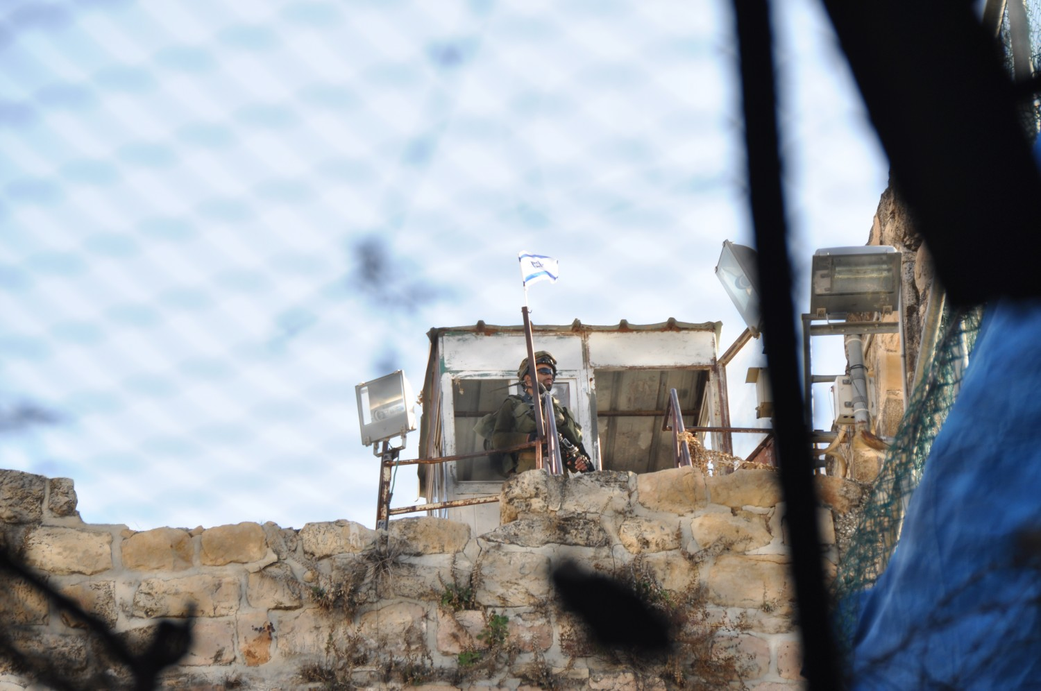 A soldier overlooking Hebron; seen through the nets