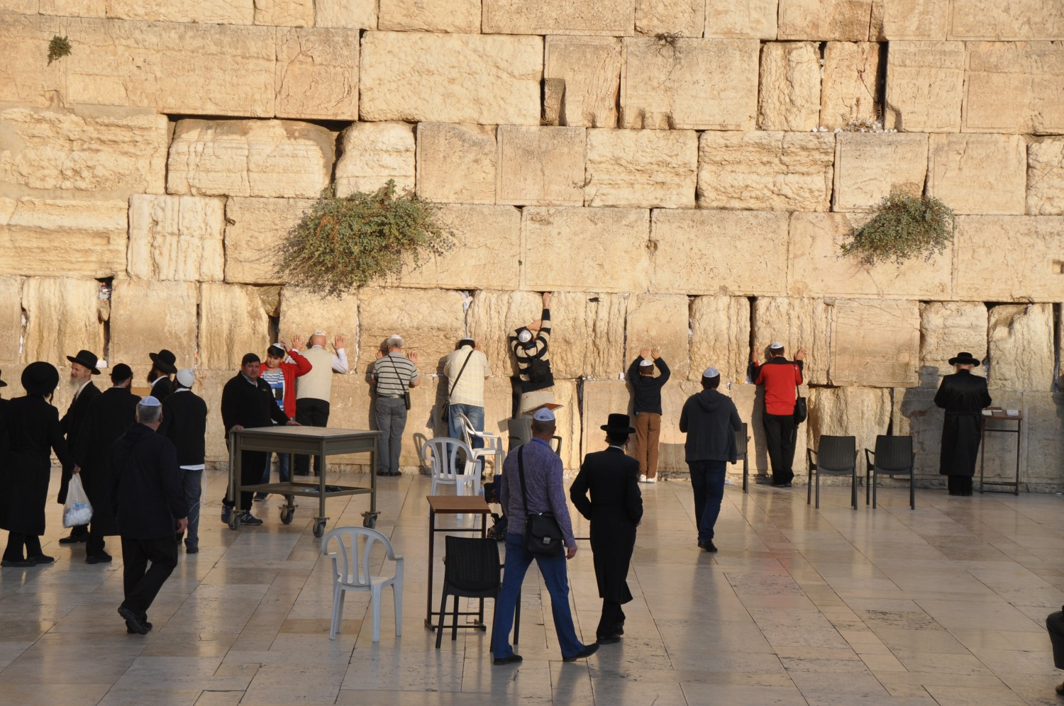People putting prayers in the cracks of the Wailing Wall